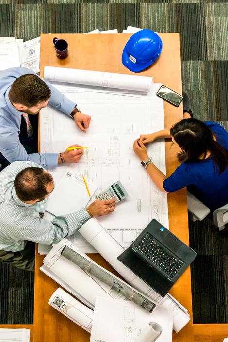 Tres personas trabajando sobre un proyecto de empresa a los que asesora GescomSL